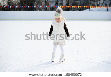 Adorable little girl in the white clothes and hat on the ice rink - stock photo