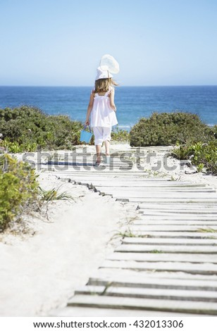 Adorable little girl in white dress going to beach in summer vacation day - stock photo