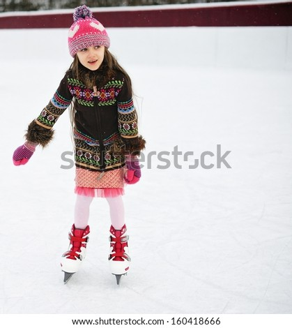 Adorable little girl in winter clothes and bobble hat skating on ice rink - stock photo