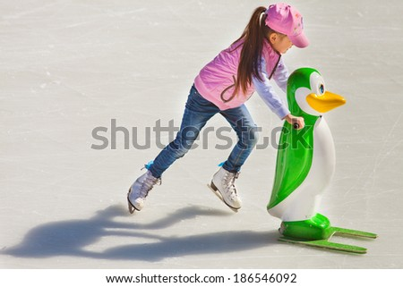 Adorable little girl in winter clothes and hat skating on ice rink at Medeo - stock photo