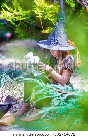 Adorable little girl in witch costume casting a spell on Halloween. Trick or treat. - stock photo
