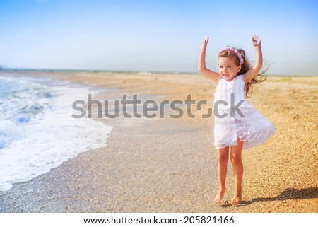 Adorable little girl jumping on the beach. happiness, holiday, wind, waves