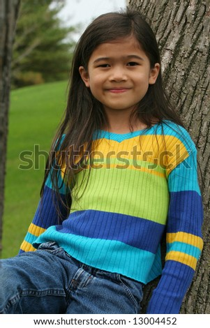 Adorable little girl leaning up against tree