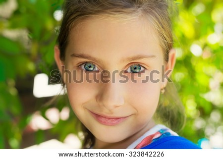 Adorable little girl looking at camera and smiling. Close up portrait. Shallow depth of field. - stock photo