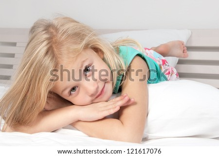 Adorable little girl looking at the camera with his arms crossed behind his head close-up - stock photo