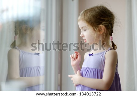 Adorable little girl looking through the window - stock photo