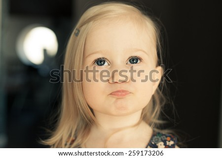 Adorable little girl looking up. Making funny lips. - stock photo