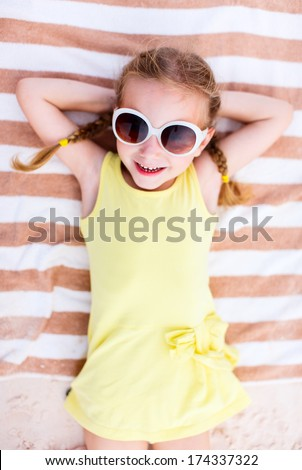 Adorable little girl lying on a beach towel during summer vacation - stock photo