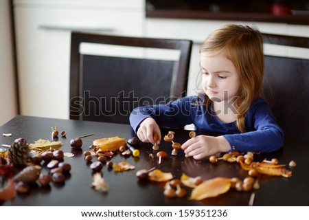 Adorable little girl making chestnuts creatures - stock photo