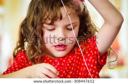 Adorable little girl making crafts at home - stock photo