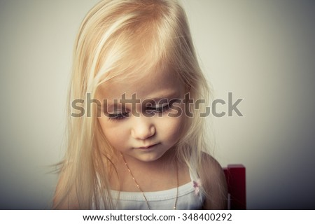 Adorable little girl making sad face. Sad look. Eyes down - stock photo