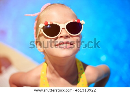 Adorable little girl near pool during tropical vacation. summer vacation concept