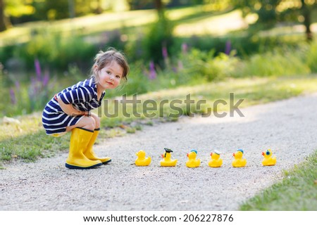 Adorable little girl of 2 playing with yellow rubber ducks in summer park. - stock photo