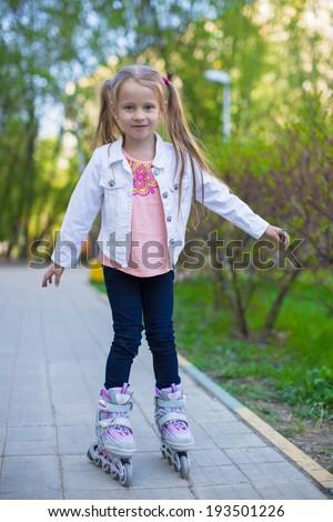 Adorable little girl on roller skates in the park - stock photo