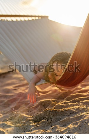 Adorable little girl on summer vacation relaxing in hammock at sunset - stock photo
