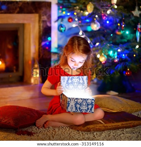 Adorable little girl opening a magical Christmas gift by a Christmas tree in cozy living room in winter - stock photo