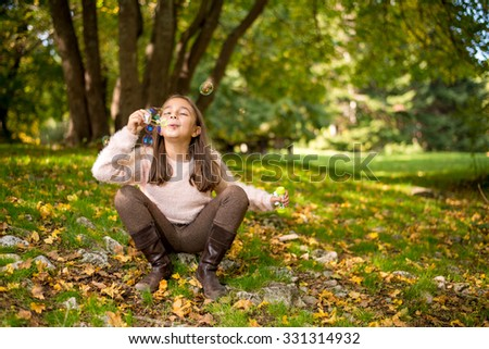 Adorable little girl outdoors at beautiful autumn day blows soap bubbles - stock photo