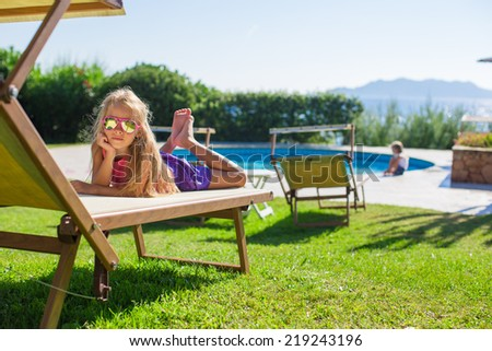 Adorable little girl outdoors on beach lounger