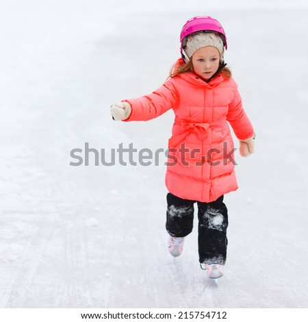 Adorable little girl outdoors on beautiful winter day ice skating - stock photo