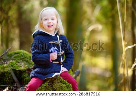 Adorable little girl picking the first flowers of spring in the woods on beautiful sunny spring day