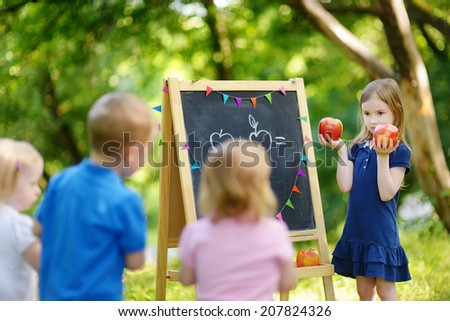 Adorable little girl playing a teacher standing by a blackboard in front of her little students - stock photo