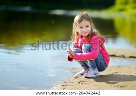 Adorable little girl playing by a river in autumn park on a beautiful sunny day