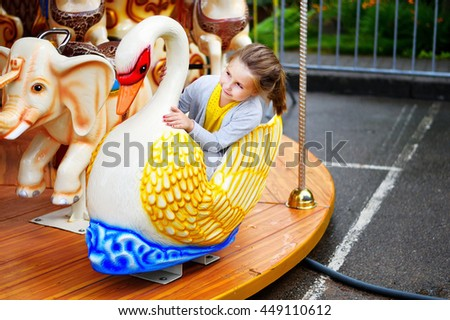 Adorable little girl playing on carousel at amusement park - stock photo