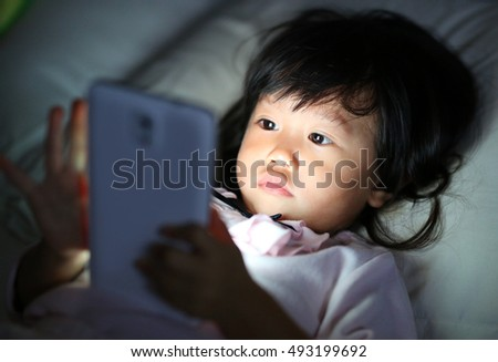 Adorable little girl playing smartphone lying on a bed at night
