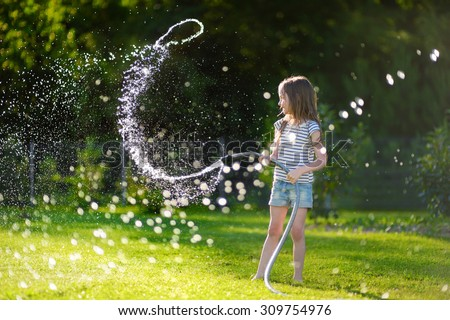 Adorable little girl playing with a garden hose on hot and sunny summer evening - stock photo