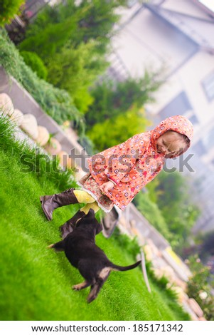 Adorable little girl playing with her puppy outdoor - stock photo