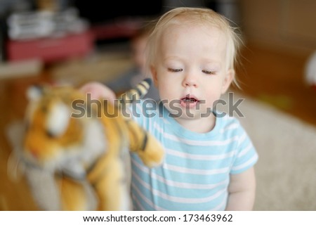 Adorable little girl playing with her toy tiger - stock photo