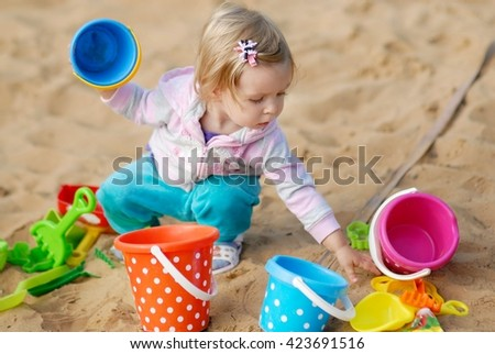Adorable little girl playing with sand - stock photo
