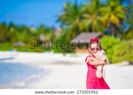 Adorable little girl playing with toy during beach vacation - stock photo