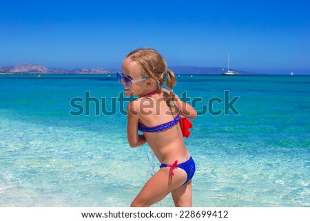 Adorable little girl playing with toy on beach vacation - stock photo