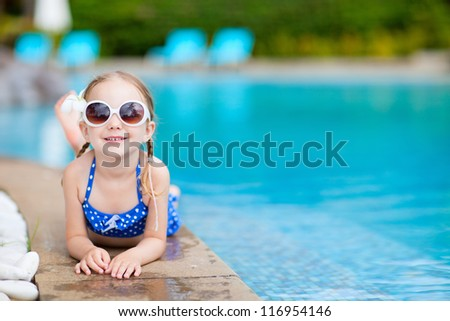 Adorable little girl relaxing by the swimming pool - stock photo