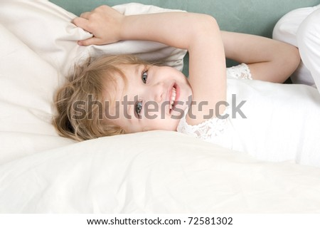 Adorable little girl resting in the bed closeup - stock photo