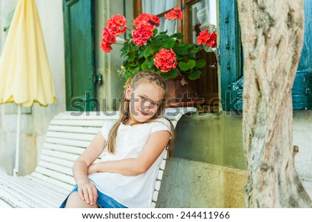 Adorable little girl resting on a bench on a nice warm summer day, outdoors - stock photo