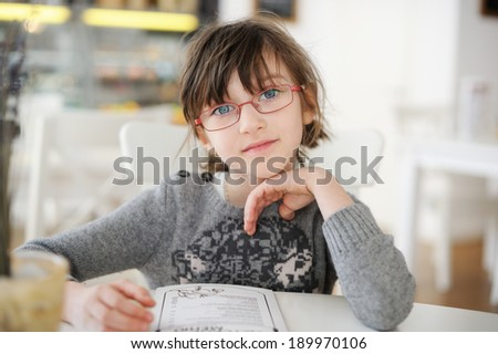Adorable little girl sitting at restaurant - stock photo