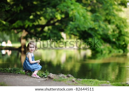 Adorable little girl sitting by the water - stock photo