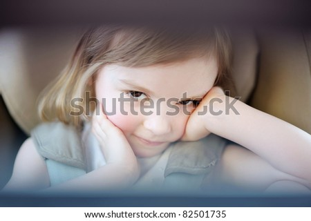 Adorable little girl sitting in a car seat - stock photo