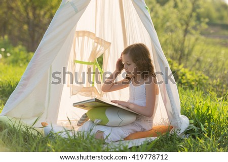 Adorable little girl sitting in a tent teepee