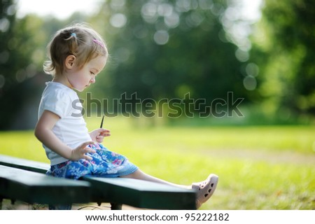 Adorable little girl sitting on a bench at summer - stock photo
