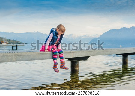 Adorable little girl sitting on a pier by the lake and swinging legs in the air - stock photo