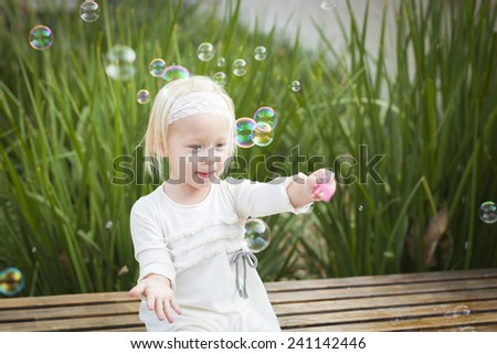 Adorable Little Girl Sitting On Bench Having Fun With Bubbles Outside. - stock photo