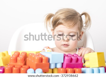 Adorable little girl sitting on chair and playing with colorful toy blocks - stock photo