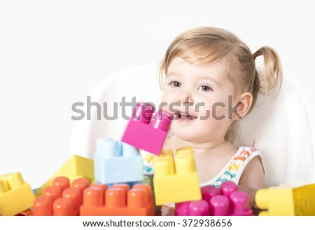 Adorable little girl sitting on chair smiling and playing with colorful toy blocks - stock photo