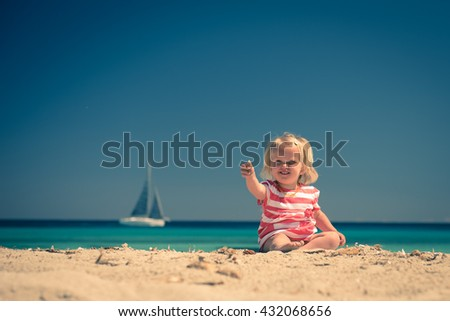 Adorable little girl sitting on  the beach and showing seashell. Instagram style toned