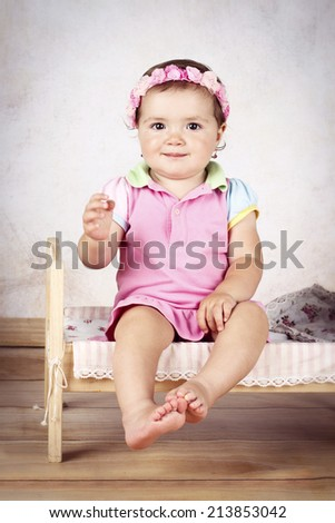 Adorable little girl sitting on the bed and wearing floral headband