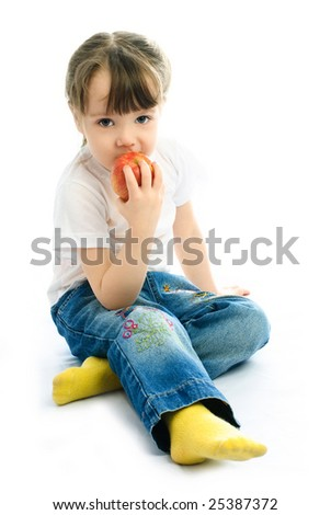 adorable little girl sitting on the floor and eating an apple - stock photo