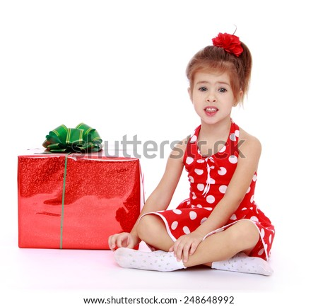 Adorable little girl sitting on the floor folding legs in Turkish, next to her is a big red beautifully wrapped gift.Isolated on white background, Lotus Children's Center - stock photo